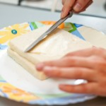 Ungem două felii de pâine cu unt pe ambele părţi