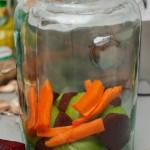 Se adaugă felii de sfeclă şi sferturi de morcov...